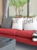 Modern woonkamerontwerp met witte hoofdkussens op rode bank Royalty-vrije Stock Fotografie