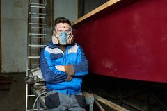 Modern Worker  in Boat Workshop. Portrait of modern worker wearing protective mask posing confidently in workshop standing next to freshly painted boat, copy Stock Images