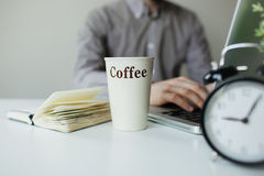 Modern working desk with laptop coffee and alarm clock Royalty Free Stock Photos