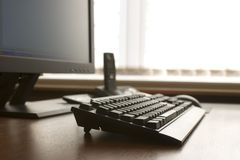 Modern workplace. Computer keyboard, tft monitor and DECT telephone on a wood desk Stock Photo