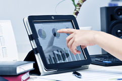 Modern workplace. Female hand touching on modern digital tablet pc at the workplace Stock Photos