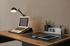 Modern workplace interior with laptop and devices on table. Space for text stock images
