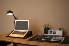 Modern workplace interior with laptop and devices on table. Space for text stock image