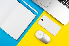 Modern workplace with notebook, computer mouse, mobile phone and white pen on blue and yellow color background Stock Photography