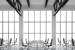 Modern workplaces in a modern bright clean interior of a loft style office. Huge windows with copy space and white walls. White de Royalty Free Stock Photography