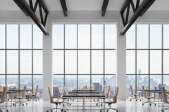 Modern workplaces in a modern bright clean interior of a loft style office. Huge windows with New York panoramic view. Black desks Stock Photo