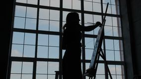 Modern workroom of contemporary fashion artist with big panoramic windows. Silhouette of a drawing female artist against royalty free illustration