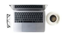 Modern workspace with coffee cup, glasses and laptop Royalty Free Stock Photo