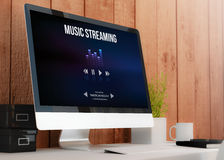 Modern workspace with computer showing music streaming website Stock Image