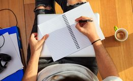 Workspace at home. Student writing, sitting on the floor Royalty Free Stock Photo