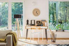 Modern workspace near window. Modern workspace located near the window with plastic chair, wooden clock and black typewriter Royalty Free Stock Image