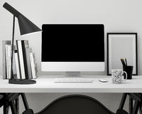 Modern workspace template mock up background. With computer monitor, keyboard, mouse, lamo, books, frame and tea mug Royalty Free Stock Photo