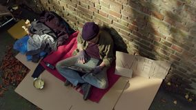 Modern world, homeless man using laptop. Tramp with no home, sitting on cardboard typing on laptop stock video