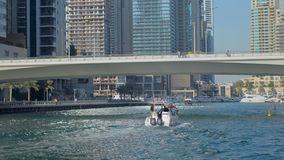 Modern yacht is floating over Dubai Marina canal in sunny day, moving under bridge. With people, urban landscape stock video footage
