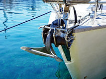 Modern Yacht Sea Anchor. A modern white hulled yacht, with detail of a withdrawn small metal sea anchor mounted on the bow Royalty Free Stock Photos