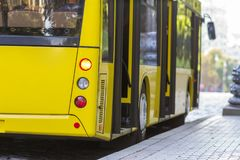 Modern yellow city bus with open doors at bus station.  Stock Photography