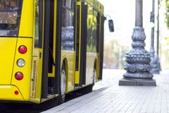 Modern yellow city bus with open doors at bus station.  Royalty Free Stock Photo