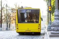 Modern yellow city bus with open doors at bus station.  Royalty Free Stock Photos