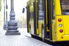 Modern yellow city bus with open doors at bus station.  Stock Photos