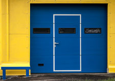 Modern yellow garage wall with closed blue gate Royalty Free Stock Photo