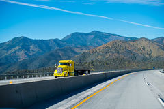 Modern yellow semi truck with flat bed trailer on scenic highway Stock Photography