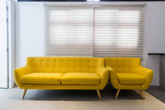 Modern yellow sofa and chair in room interior at home or hotel stock images