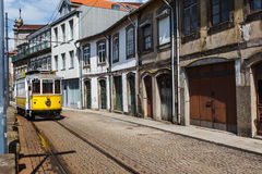 Modern yellow and white trolley proceeds down narrow city street in Porto, Portugal. Modern yellow and white trolley proceeds down narrow city street in the Royalty Free Stock Image