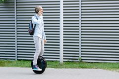 Business man male with electric transport unicycle. Modern young adult male businessman student freelancer riding driving on ecological electric transport royalty free stock photo