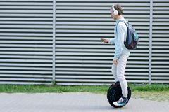 Business man male with electric transport unicycle. Modern young adult male businessman student freelancer riding driving on ecological electric transport royalty free stock images