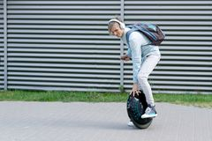 Business man male with electric transport unicycle. Modern young adult male businessman student freelancer riding driving on ecological electric transport stock image