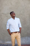 Modern young black man smiling with hands in pockets. Portrait of modern young black man smiling with hands in pockets Stock Photography