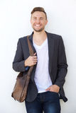 Modern young business man with bag smiling against white wall Royalty Free Stock Image