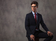 Modern young business man wearing glasses and sits on stool Stock Photos