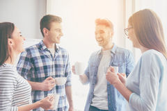Modern young business people. Best team. Positive and laughing young business people talking while coffee break in their office and enjoying their time Royalty Free Stock Images