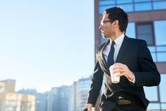 Morning haste. Modern young businessman with glass of coffee and briefcase hurrying for briefing in urban environment in the morning stock photo