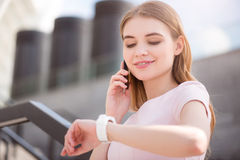 Modern young businesswoman. Being in time. Smiling and confident young businesswoman talking on a phone and checking time at a smart watch Royalty Free Stock Image