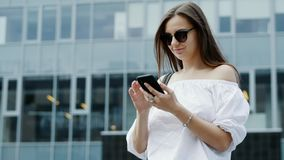 Modern young businesswoman holding mobile phone, woman texting messages, chatting with colleagues, browsing the internet stock footage