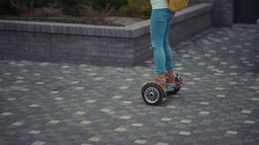 Modern young girl with a bright yellow backpack rides on hoverboard