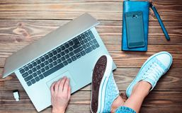 A modern young girl sits on a wooden floor and enjoys a laptop. Generation z. The concept of freelancing. Working space. Top view Royalty Free Stock Images