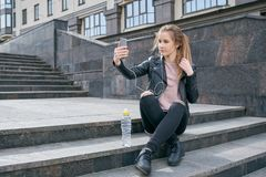 Modern young girl teenager resting on the stairs while walking around the city. The concept of modern gadgets, selfie. Social networking Royalty Free Stock Image