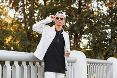 Modern young hipster man in a summer white jacket in sunglasses in a trendy jeans t-shirt poses in a park near a metal fence. Nice guy model enjoying the royalty free stock photography