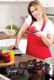 Modern young housewife using a laptop while cooking Stock Photos