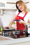 Modern young housewife using a laptop while cooking Stock Photography