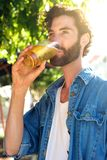 Modern young man drinking beer in summer at outdoor bar Royalty Free Stock Photography