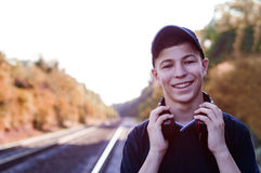 Teenager with headphones listens to music on the railway tracks Royalty Free Stock Photo