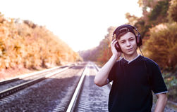 Teenager with headphones listens to music on the railway tracks. Modern young man with headphones listening to music on the railway tracks Royalty Free Stock Image