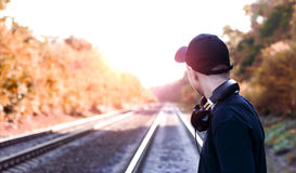 Teenager with headphones listens to music on the railway tracks Stock Image