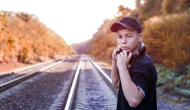 Teenager with headphones listens to music on the railway tracks Stock Photo