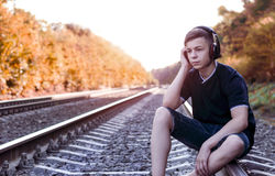 Teenager with headphones listens to music on the railway tracks Royalty Free Stock Images