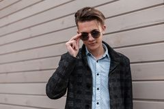 Modern young man hipster with stylish hairstyle in trendy sunglasses in a elegant gray jacket in a classic shirt poses. Near a vintage wooden building outdoors royalty free stock photos